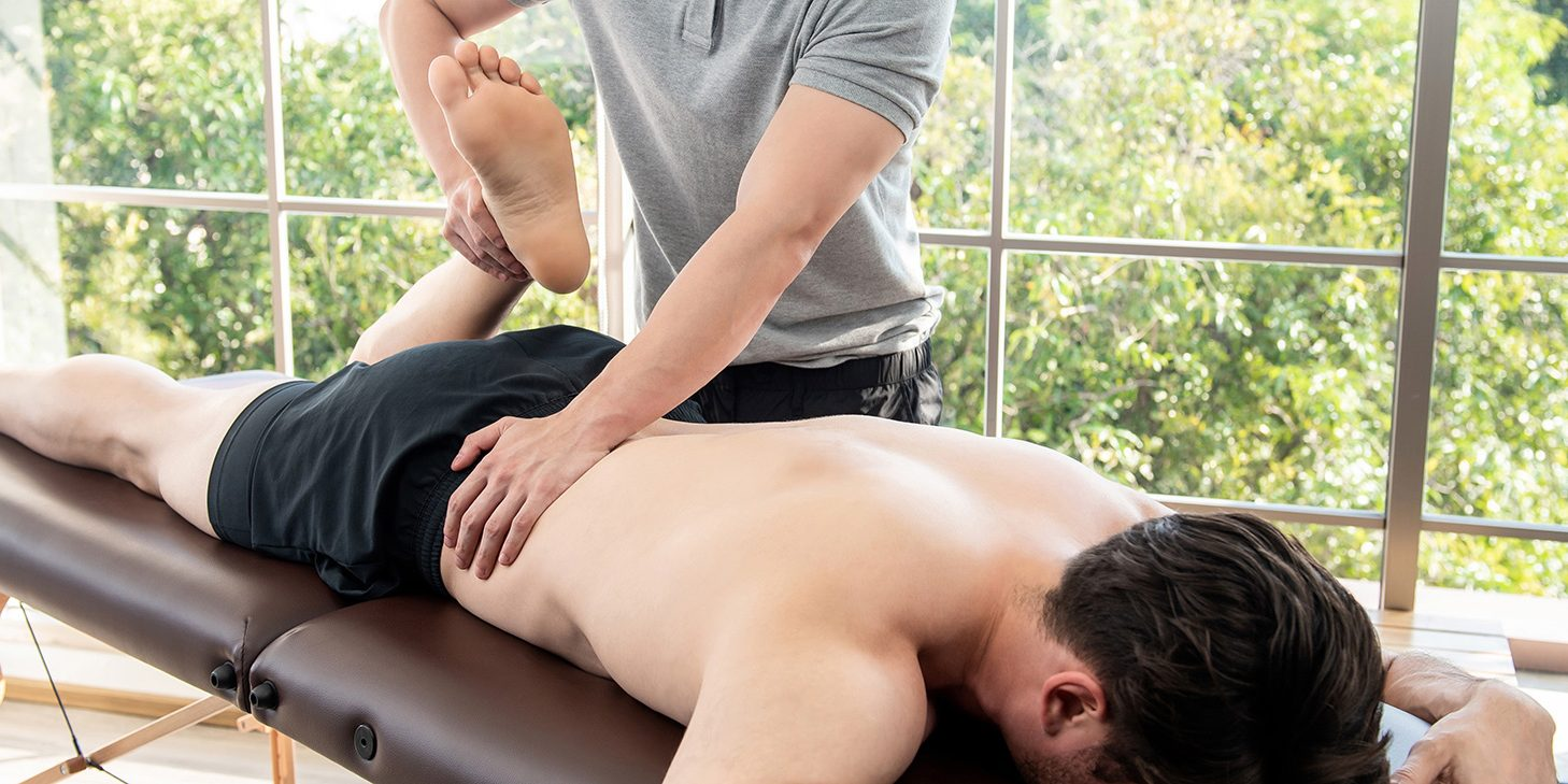 physiotherapist-giving-massage-stretching-male-patient-clinic